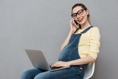 Dame heureuse enceinte à l'aide de l'ordinateur portable et parlant par le téléphone Image stock