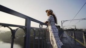 Dame in hoed en kleding die zich op brug bevinden en zonsopgang bekijken stock video