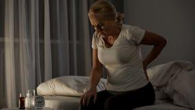 Dame in ihren 50 kann nicht schlafen wegen der akuten Schmerz in der unteren Rückseite und in den Nieren, Gesundheit lizenzfreies stockfoto