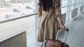 Dame im beige Mantel mit dem schwarzen Haar trägt Koffer stock video