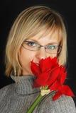 Dame im grauen Kleid mit roter Blume auf Schwarzem. Stockfotos