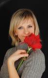 Dame im grauen Kleid mit roter Blume auf Schwarzem. Stockbilder