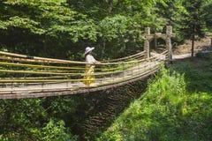 Dame im Hut, der auf der Hängebrücke steht Stockfoto