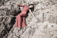 Dame im Kleid, das in den Schmutz legt lizenzfreie stockbilder