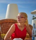 Dame im Rot gesetzt Stangen-Terrasse an der im Freien Lizenzfreie Stockfotos