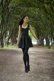 Dame im schwarzen Kleid im Sommerpark Stockfotos