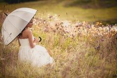 Dame im Weiß mit Regenschirm auf der Wiese Lizenzfreie Stockfotos