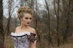 Dame im Weinlesekleid im Wald, Berufsmake-up, Haare Stockbild