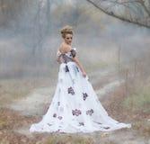 Dame im Weinlesekleid im Wald im Nebel Stockbilder