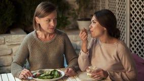 Dame jalouse mangeant de la salade végétale regardant l'ami goûtant le dessert crémeux image libre de droits