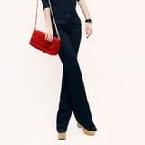 Dame in klassieke zwarte broeken en zwarte blouse met een rode clutc stock afbeelding