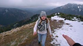 Dame klettert den Berg und die Führer ` s Hand hilft ihr zu klettern stock video