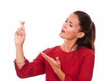 Dame latine attirante avec souhaiter le signe photo stock