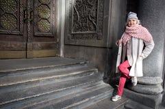 Dame mûre autosuffisante se tenant près de la porte architecturale Images stock