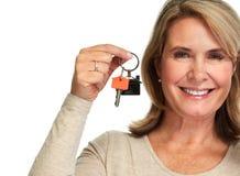 Dame mûre avec une clé de maison photo stock