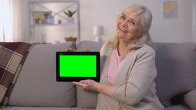 Dame mûre de sourire tenant le comprimé vert d'écran dans des mains, opérations bancaires faciles, achats clips vidéos