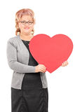 Dame mûre tenant une grande pose rouge de coeur Image stock