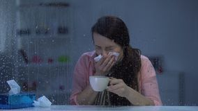 Dame malade dans l'écharpe éternuant et buvant du thé chaud à la maison le jour pluvieux, virus de grippe clips vidéos
