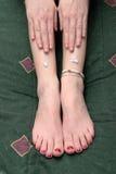 Dame met lotion op haar benen stock afbeelding