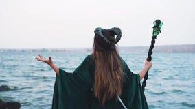 Dame met zwarte grote hoornen op hoofd in lange groene kleding met gouden riem met magische band in hand dichtbijgelegen rivier,  stock videobeelden