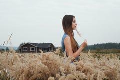 Dame mignonne de campagne se tenant dans l'herbe grande contre le ranch Images libres de droits