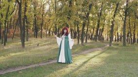 Dame mignonne modeste avec les cheveux courbés rouges, grand modèle dodu dans la pomme nationale lâche verte de participation de  banque de vidéos