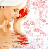 Dame mit den roten Blumenblättern und den Blumen im Wasser Lizenzfreies Stockfoto