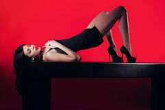 Dame mit ledernem Kragen mit Bolzen auf einem roten Hintergrund Stockbild
