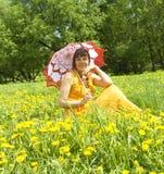 Dame mit Regenschirm und gelbem Löwenzahn Stockfoto