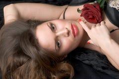 Dame mit roter Blume gegen schwarzen Hintergrund Stockfoto