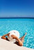 Dame mit weißem Hut entspannt sich im Swimmingpool Stockfotografie