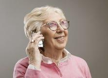 Dame a?n?e heureuse parlant au t?l?phone photographie stock libre de droits