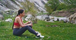 Dame nach einem Training mitten in durstigem Getränk der Natur etwas Wasser und einen Bruch unter Verwendung eines Smartphone zum