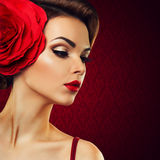 Dame passionnée avec une fleur rouge dans ses cheveux. Photos stock