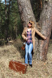 Dame-photographe avec la vieille valise d'appareil-photo et de vintage sous le grand pin Photos stock