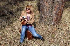 Dame-photographe avec le vieil appareil-photo se reposant sur une valise de vintage dans l'herbe sèche Images stock