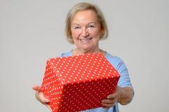 Dame pluse âgé attirante avec un grand cadeau de Noël Images libres de droits