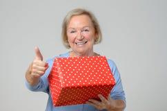 Dame pluse âgé attirante avec un grand cadeau de Noël Images stock