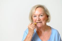 Dame pluse âgé employant la brosse interdentaire Photos stock