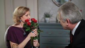 Dame pluse âgé heureuse recevant des fleurs de l'homme clips vidéos
