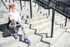 Dame pluse âgé joyeuse à l'aide du smartphone tout en se reposant sur la structure d'étapes Image libre de droits
