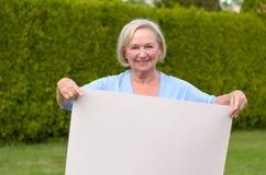 Dame pluse âgé montrant un tableau blanc vide Photo stock