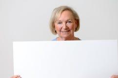 Dame pluse âgé montrant un tableau blanc vide Photos libres de droits