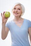 Dame pluse âgé positive en bonne santé posant avec la pomme Photo libre de droits