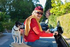 Dame pluse âgé prenant son chien pour un tour de scooter Photographie stock libre de droits