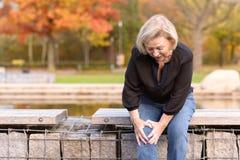 Dame pluse âgé saisissant son genou en douleur images libres de droits