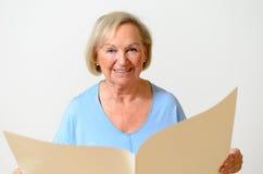 Dame pluse âgé tenant un papier blanc Photo stock