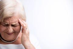 Dame pluse âgé touchant sa tête avec des doigts Images stock