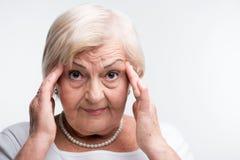 Dame pluse âgé touchant sa tête avec des doigts Images libres de droits