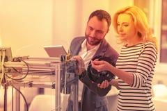 Dame qualifiée et monsieur compétents réparant l'imprimante 3D endommagée photo libre de droits
